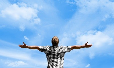 Young man with outstretched arms embracing life